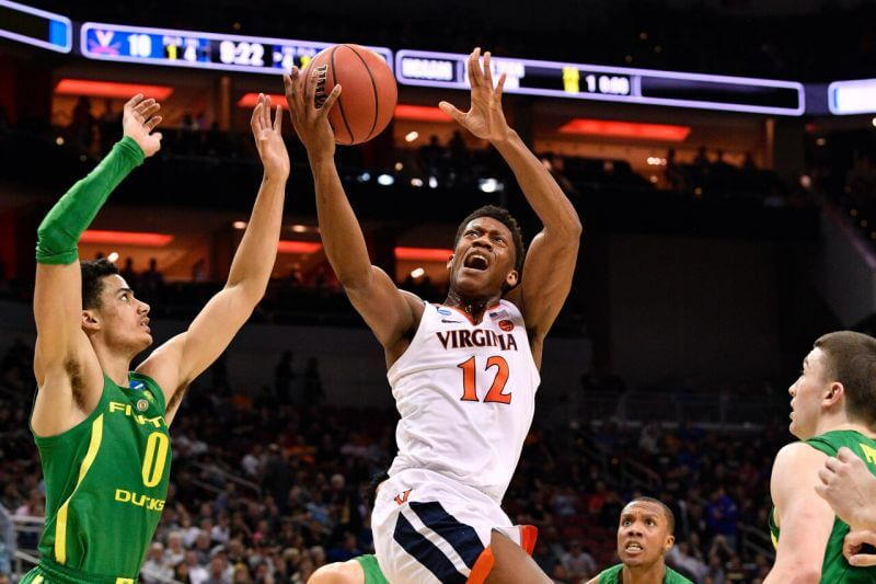 Virginia Cavaliers guard De'Andre Hunter goes up for a shot as Oregon Ducks guard Will Richardson defends during the first half in the semifinals of the south regional of the 2019 NCAA Tournament on Mar. 28, 2019, in Louisville, KY.